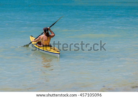 Young woman kayaking in the sea - selective focus, copy space