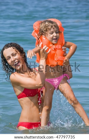 young woman keeps in hands little girl in life-jackets in sea on resort