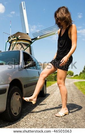 Young woman kicking angrily at the tire of her broken car on a rural road on a beautiful summer day - stock photo