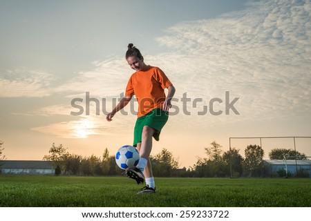 young woman kicking soccer ball - stock photo