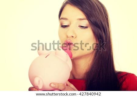 Young woman kissing a piggybank. - stock photo