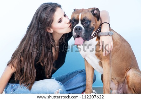 Young woman Kissing her dog. Portrait of Pretty young, happy, woman with her beautiful Boxer Dog. Studio shoot. Blue , white background