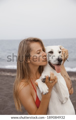 Young woman Kissing her dog. Portrait of Pretty young, happy, woman with her beautiful puppy. Shot on the beach. vertical - stock photo
