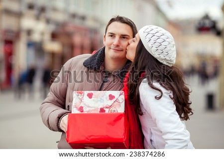 Young woman kissing young man holding gift boxes - stock photo