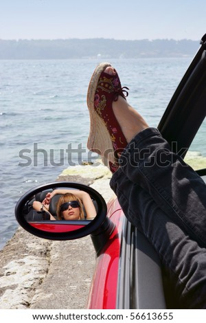 Young woman laid in a car face to the sea - stock photo