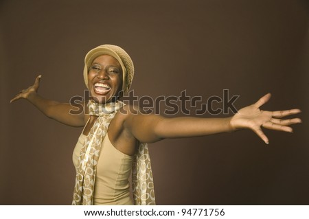 Young woman laughing with outstretched arms - stock photo