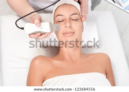 Young woman laying eyes closed, getting facial beauty treatment, view from above. - stock photo
