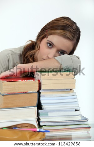 Young woman laying her head on a stack of books - stock photo