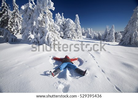 Young woman laying on snow and making snow-angel