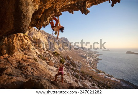 Young woman lead climbing along a roof in cave with beautiful view in background  - stock photo