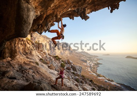 Young woman lead climbing in cave with beautiful view in background  - stock photo