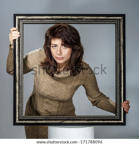 Young woman lean out from picture frame  isolated on grey background