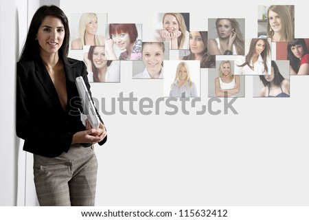 Young woman leaning against a white wall holding a white laptop computer displaying the concept of network connection. - stock photo
