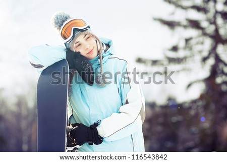 Young woman leaning on her snowboard, she's looking away and smiling; copy space, close up, lens flare