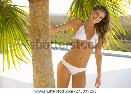 Young woman leaning on palm tree. - stock photo