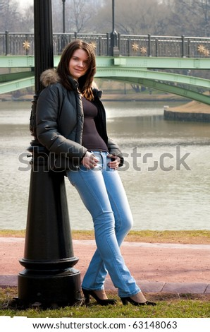 Young woman leans lamppost in autumnal park