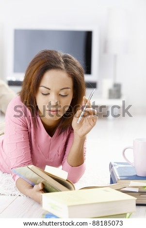 Young woman learning at home, reading book, lying on floor, holding pen.? - stock photo