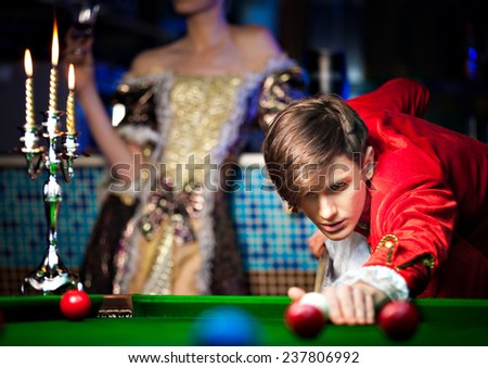 Young woman learning how to play billiard with the help of a young man - stock photo