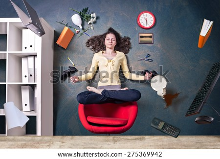 young woman levitating by a yoga pose in the office - stock photo