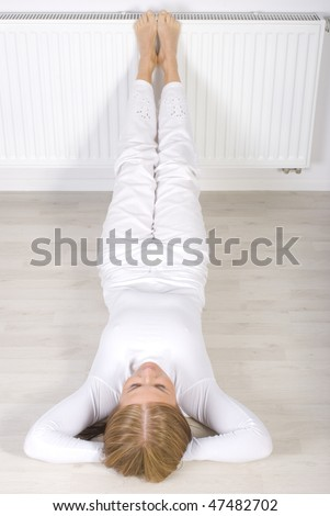 Young woman lie on floor near radiator - stock photo