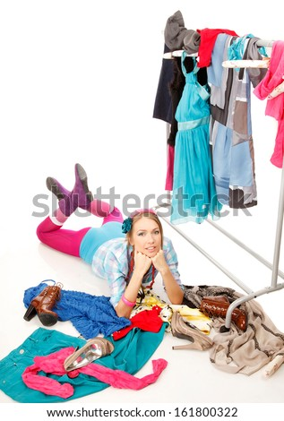 Young woman lies near her clothes rack with lots of dresses,and some clothes is on the floor - stock photo