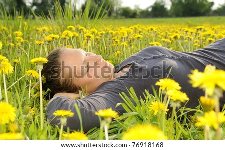 young woman lies on a flower meadow