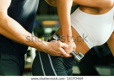 Young woman lifting a dumbbell in the gym assisted by her personal trainer (Close-up, no faces to be seen) - stock photo