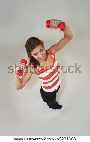Young woman lifting dumbbells - stock photo