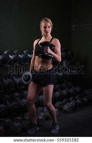 Young woman lifting free weights at a gym.