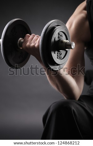 Young woman lifting the dumbbells, close up - stock photo