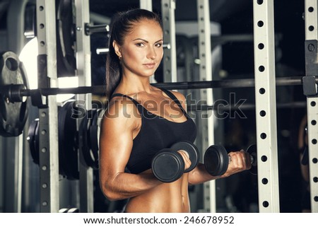 Young woman lifting the dumbbells in the gym, fitness - stock photo
