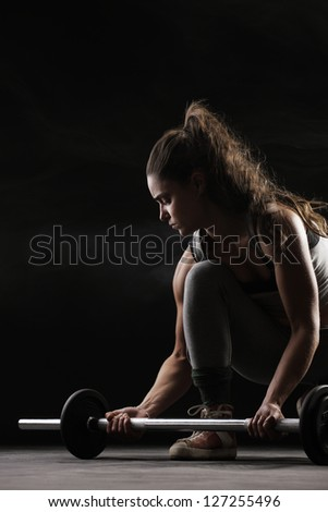 Young woman lifting weights - stock photo