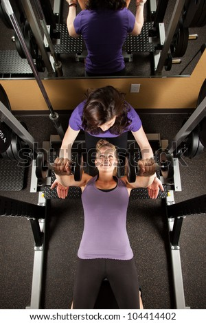 Young Woman Lifting Weights with Personal Trainer - stock photo