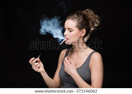 young woman lighting a cigarette, smoking concept on black background