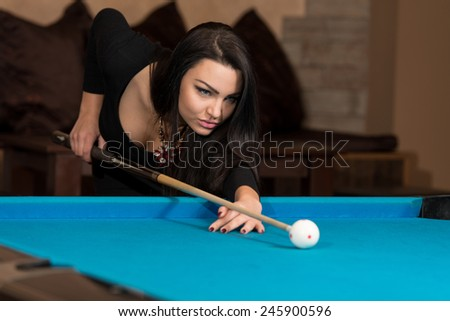 Young Woman Lining To Hit Ball On Pool Table - stock photo
