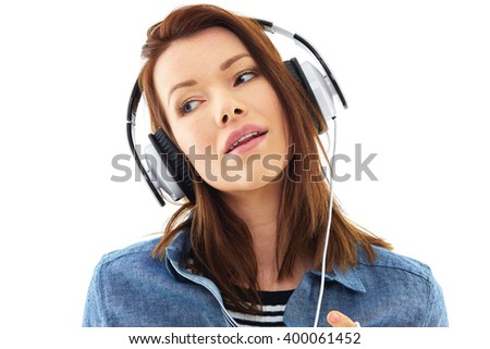 Young woman listen to music on her white headphones, isolated over white background - stock photo