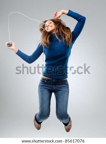 Young woman listening and dancing to music with earphones, having fun and relaxing - stock photo
