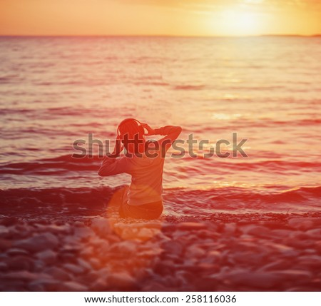 Young woman listening music on beach and enjoying beautiful sunset over the sea. Image with sunlight effect - stock photo