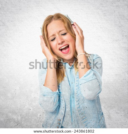Young woman listening music over textured background - stock photo