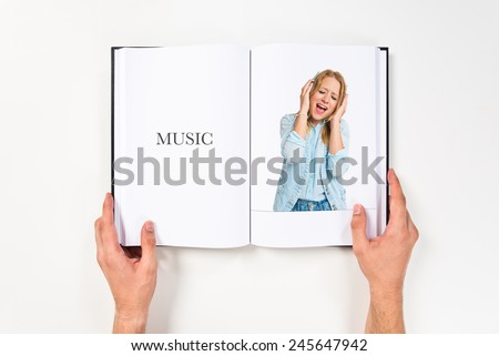 Young woman listening music printed on book - stock photo