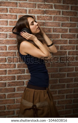Young woman listening music while leaning on a brick wall with her eyes closed, using wireless headphones - stock photo