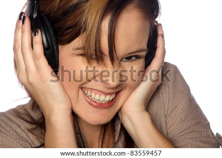 Young woman listening to music and smiling - stock photo