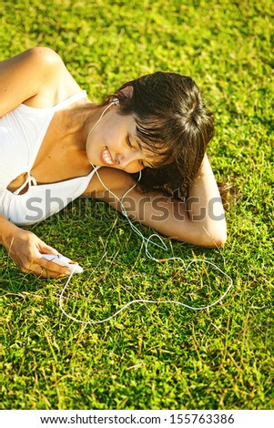 young woman listening to music on her mobile phone in park