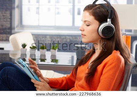 Young woman listening to music on tablet through headphones. Side view. - stock photo