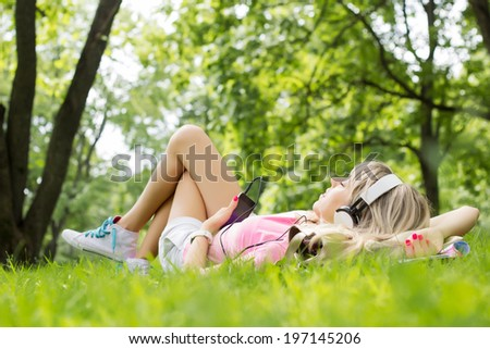 Young woman listening to music while lying down on grass - stock photo