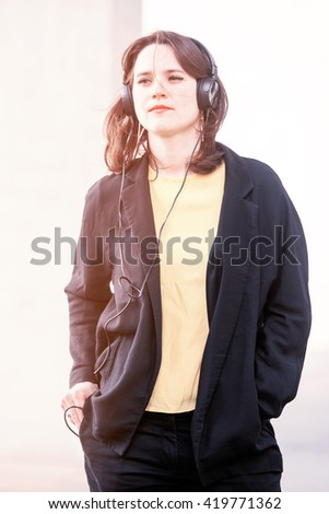 young woman listening to music with headphones - stock photo