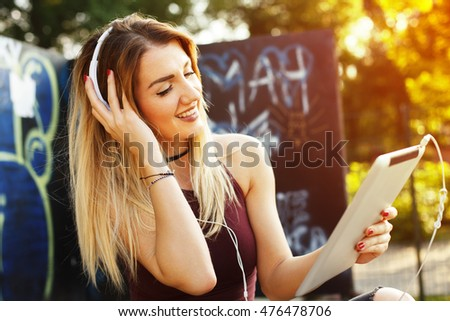 Young woman listening to music with headphones via digital tablet