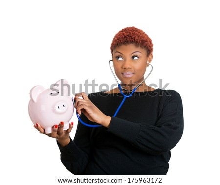 Young woman listening to piggy bank with stethoscope. Medical insurance, medicare reimbursement concept . Curious nurse, doctor, patient or business lady. Health-law coverage gap or company report  - stock photo