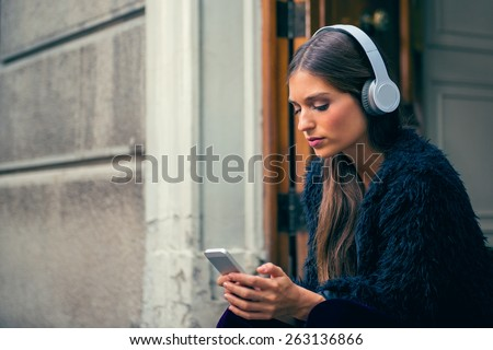 Young woman listens music on the street with on line music application. - stock photo