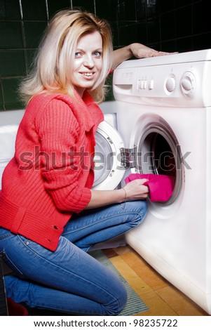 Young woman loading the washing machine - stock photo